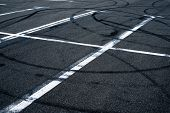 pic of paved road  - Asphalt surface of the empty parking with white road marking lines and wheel tracks - JPG