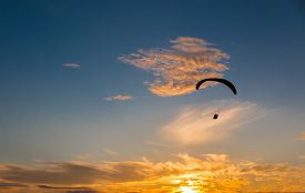 picture of glider  - A para glider soars into a beautiful pacific sunset - JPG