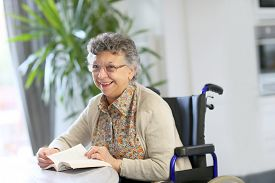 foto of wheelchair  - Elderly woman in wheelchair reading book - JPG