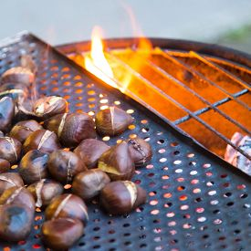 stock photo of stall  - Grilling chestnuts being sold at stalls in autumn. ** Note: Soft Focus at 100%, best at smaller sizes - JPG