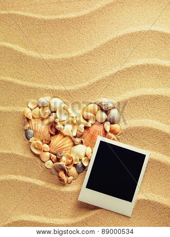 Heart made of sea shells and starfish is lying on the beach sea sand with vintage empty photo cards. Summer style background. Space for your text.