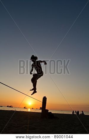 Silhouette of young man balancing on slackline at a beach in Manabi, Ecuador