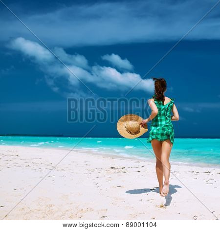 Woman in green dress at tropical beach