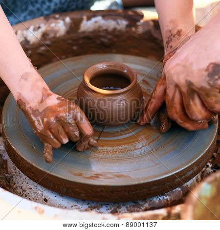 Potter's hands guiding child's hands to help him to work with the pottery wheel