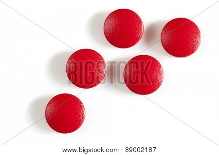 Red iron supplement pills, isolated on white.  Overhead view.