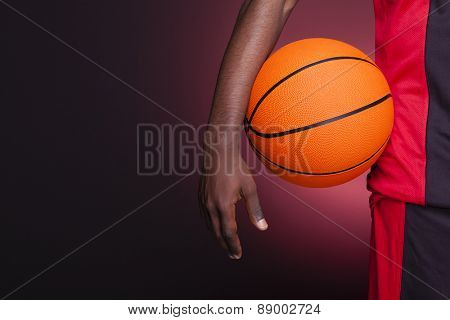 Detail of a basketball player holding a ball against dark background