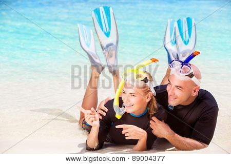 Joyful diver couple lying down on the beach, wearing mask and flippers for snorkeling, looking on the side and showing on something, active summer time vacation
