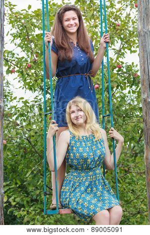 Young girls on handmade swing in summer apple trees garden