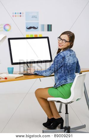 Woman working at desk In a creative office, using a computer
