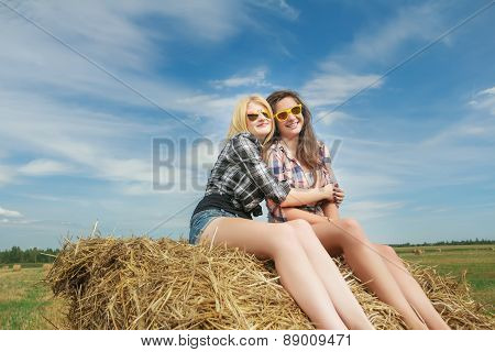 Portrait of leggy blonde and brunette girls posing on bundle of straw