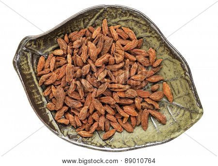 dried goji berries (wolfberry in a leaf shaped ceramic bowl isolated on white