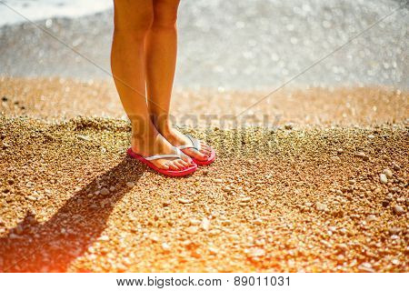 Woman's legs in slippers on the beach