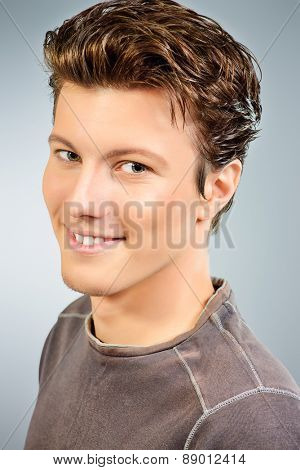 Close-up portrait of a smiling young man in t-shirt. Men's beauty, fashion. Studio shot.