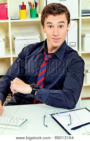 Surprised businessman looking at his watch at the office. Time concept.
