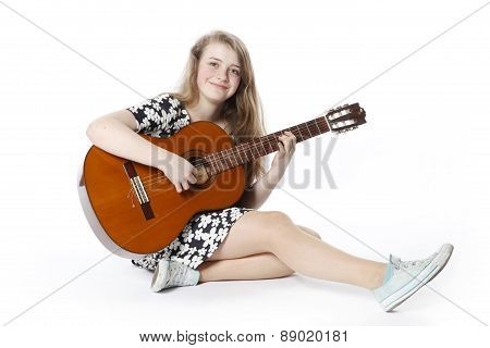 Smiling Teenage Girl In Dress Plays The Guitar .sitting On The Floor