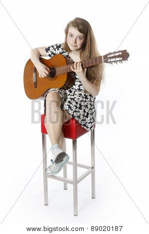 Smiling Teenage Girl In Dress Plays The Guitar In Studio.sitting On High Red Stool