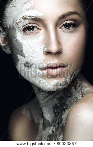 Beautiful girl with mud on his face. Cosmetic mask. Beauty face.
