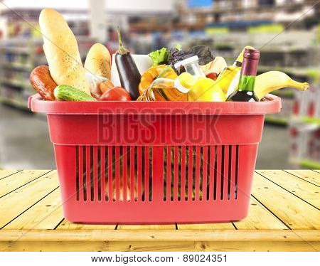 Brown table and on background blured supermarket and basket with products