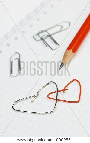 Paper clips formed as hearts and a pencil