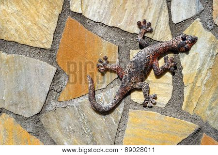 Gecko made of metal on a stone wall