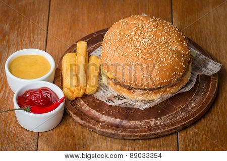 Delicious Burger On Paper With Sauces And Fries