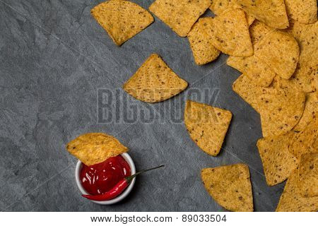 Nachos With Hot Salsa Sauce And A Red Hot Chili Pepper