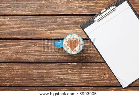 Cappuccino And Business Tablet With Paper On Wooden Table.