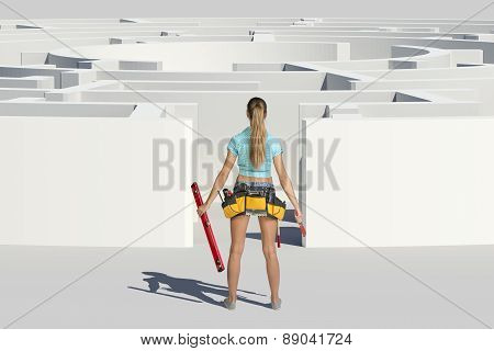 Young woman standing back with tools