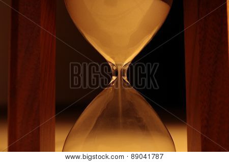 Sand pours in hourglass