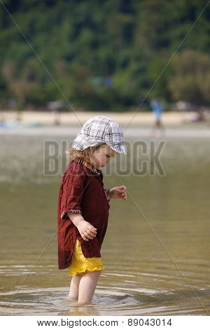 Child Walking On Fine Sand Through The Water