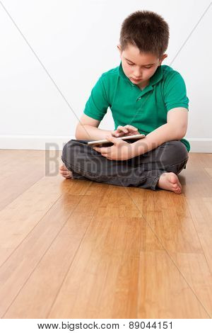 Cute Male Kid Sitting On The Floor With Tablet