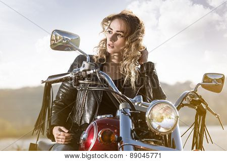 Biker girl in  leather jacket on a motorcycle looking at the sunset.