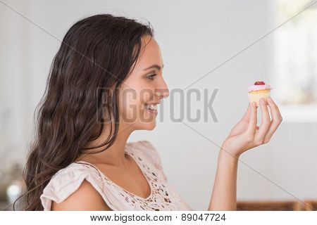 Beautiful brunette holding mini cupcake in the kitchen