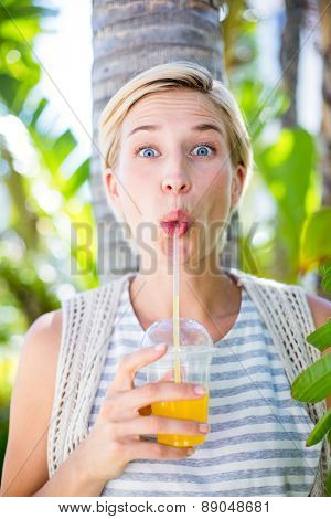 Pretty blonde woman smiling at the camera and drinking orange juice in the park
