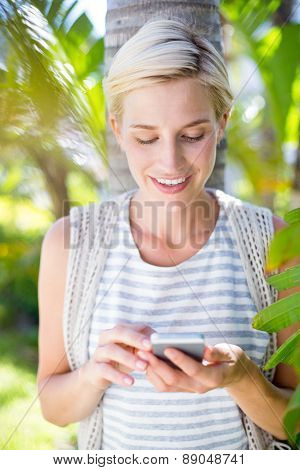 Pretty blonde woman texting with her mobile phone in the park