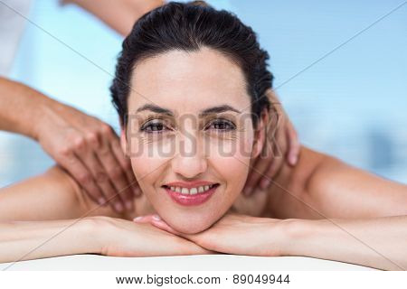 Smiling brunette getting back massage in a healthy spa