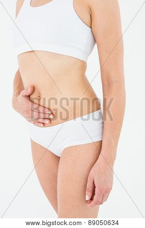 Fit woman suffering from stomach pain on white background