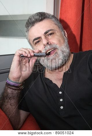 Attractive Senior With White Beard Smoking Electronic Cigarette