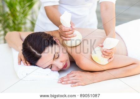 Brunette having massage with herbal compresses in the health spa