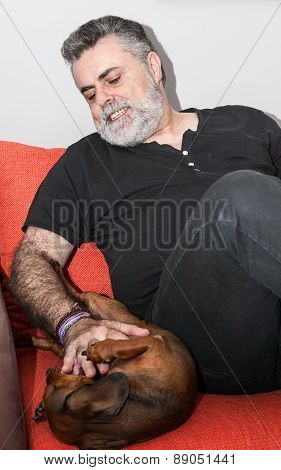Attractive Senior With White Beard Playing With Dachshund Dog