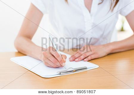Businesswoman taking notes on white background