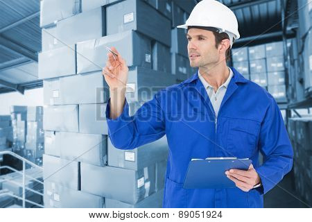 Supervisor inspecting while holding clip board against shelves with boxes in warehouse
