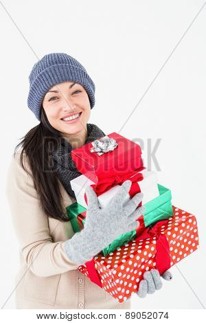 Happy brunette holding gifts on white background
