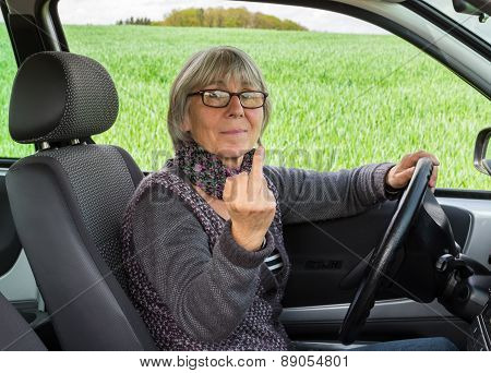 Senior Woman In The Car Shows Middle Finger