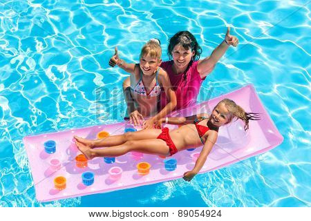 Family with children in swimming pool. Summer outdoor. Gesture thumb up.