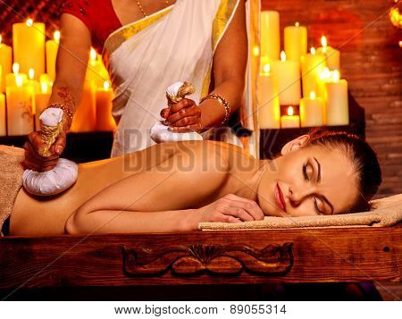 Woman having ayurvedic massage with pouch of rice. Burning candloe.