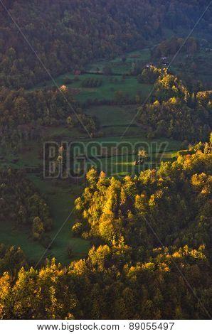 Meadow illumintad by ray of light at autumn sunrise