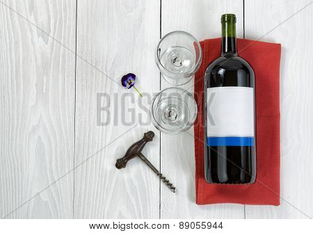 Large Bottle Of Red Wine On Serving Napkin With Glasses On White Wooden Boards