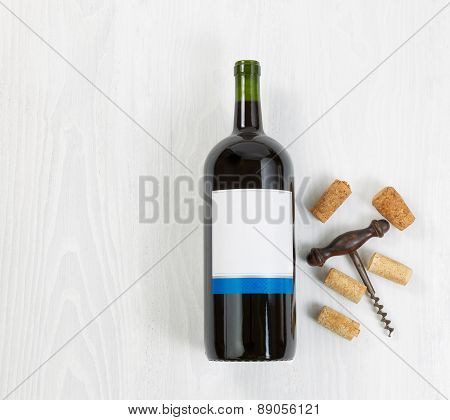 Large Bottle Of Red Wine With An Antique Corkscrew And Old Corks On White Wood