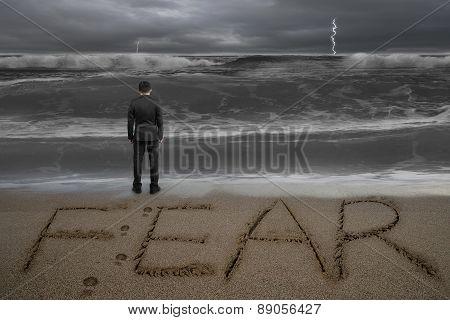 Rear View Businessman Standing Facing Fear Word On Sand Beach